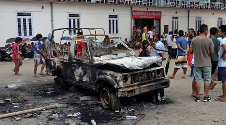 People gather near a damaged vehicle after it was set on fire during a protest in Manipur (PTI Photo)